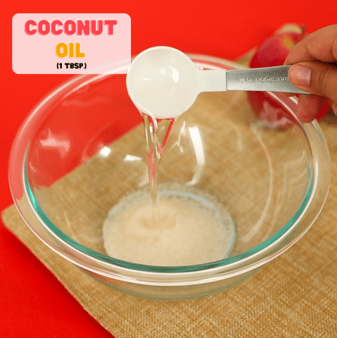 measuring spoon pouring coconut oil into a bowl