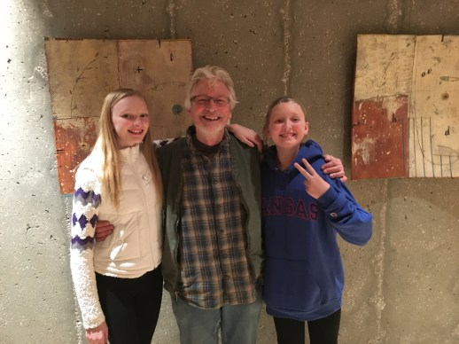 Steven Hill pauses to pose with two Bede Clarke wall pieces, and two Cindy Bracker daughters.