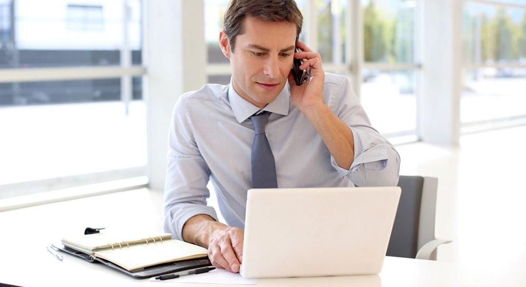 Vendedor negociando no smartphone e laptop