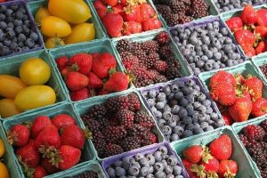 Blue cardboard boxes full of fresh strawberries, blueberries, and raspberries.