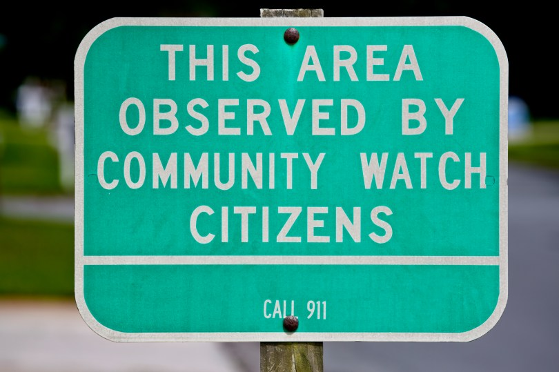 Community Watch Sign with Neighborhood in Background Close Up
