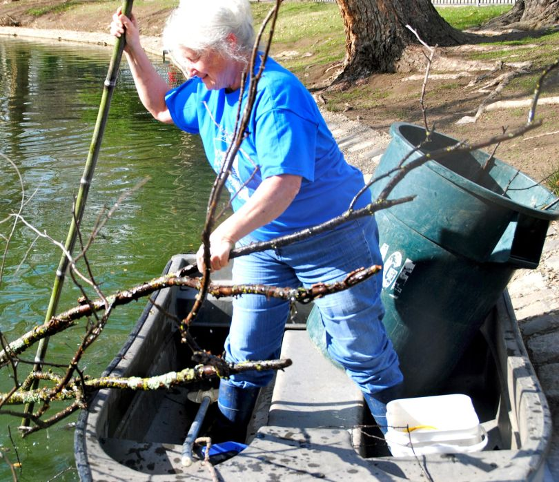 Judy working from a boat to clean trash and debris out of McKinley Pond.