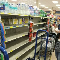 view post A shopper in Sedano's Supermarket looks at nearly empty water shelves in the Little Havana neighborhood in Miami