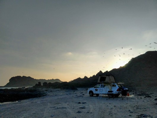Auto mit Dachzelt am Strand bei Sonnenaufgang