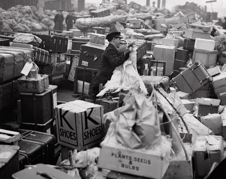 A station luggage handler surrounded by Christmas parcels and suitcases at Waterloo, December 1936. (Img ref: 10308463).