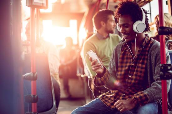 Student listening to headphones while on a bus