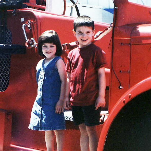 Rebecca Delevati and her twin brother, Stephen, as children standing in front of a fire truck.