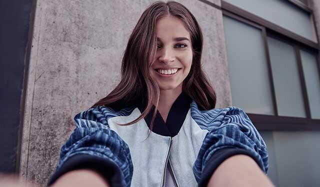 Una mujer joven con cabello de color café y con una chaqueta deportiva blanca, negra y azul sonríe mientras se toma una selfie.