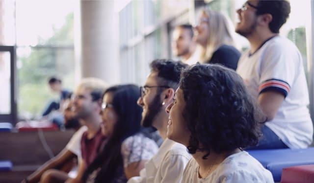 un grupo de personas de equipo de Nubank, el mayor banco digital del mundo, sonríe en una reunión grupal