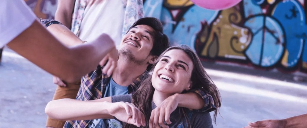 Una pareja abrazada y riendo sentadas en la calle.