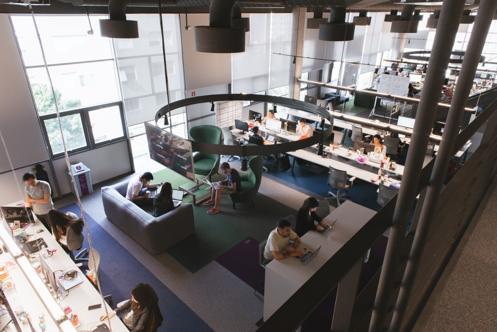 Un amplio espacio visto de arriba con personas trabajando en un sillón gris de dos cuerpos, dos de color verde de un cuerpo y el resto de las personas en sillas con sus computadoras.