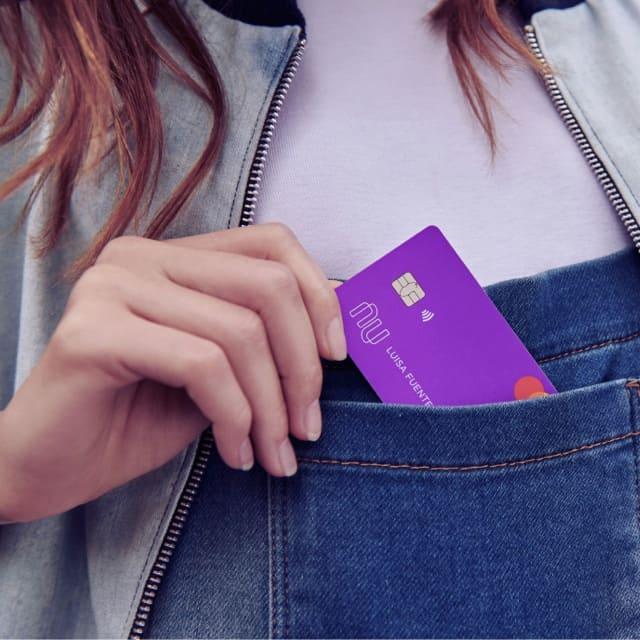 La tarjeta de crédito Nu, morada y poderosa, sale de la bolsa de una camisa de mezclilla