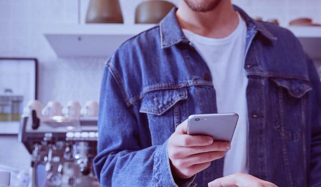 Hombre vestido en mezclilla usa su celular para consultar el saldo en tiempo real de su tarjeta de crédito Nu, desde la app de Nubank.