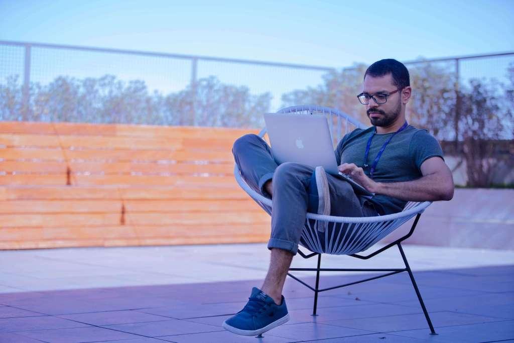 Chico  sentado en silla de terraza toma cursos gratuitos sobre finanzas personales en su computadora posrtatil