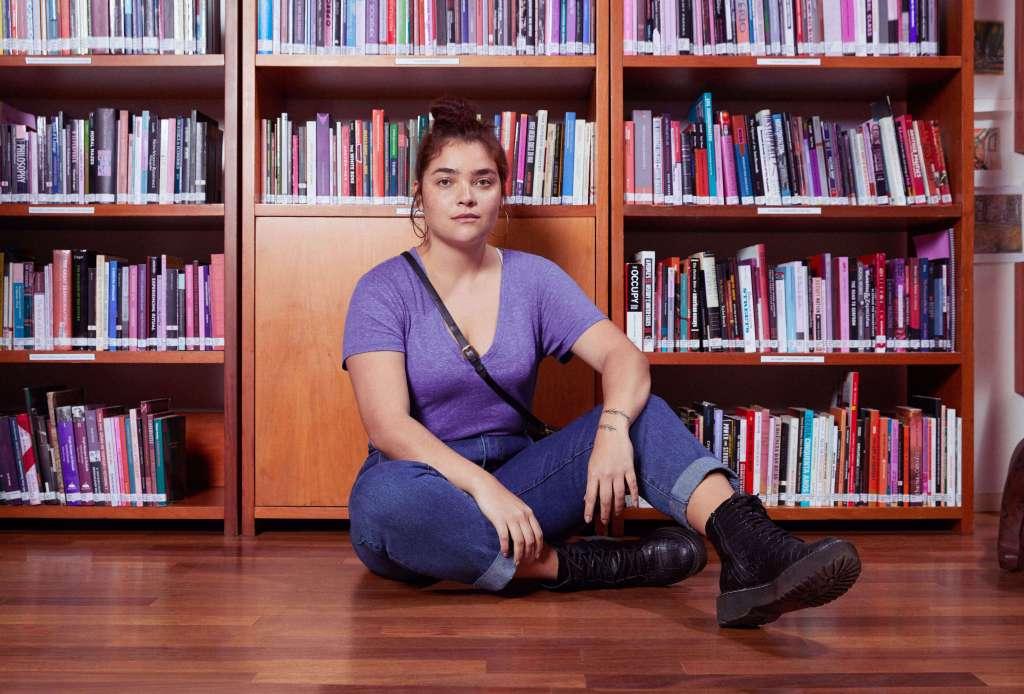 Mujer pelirroja de mediana edad usa una playera morada y jeans con botas negras, se encuentra sentada en el piso de una biblioteca meditando acerca de dinero y cuestiones de finanzas personales para la mujer