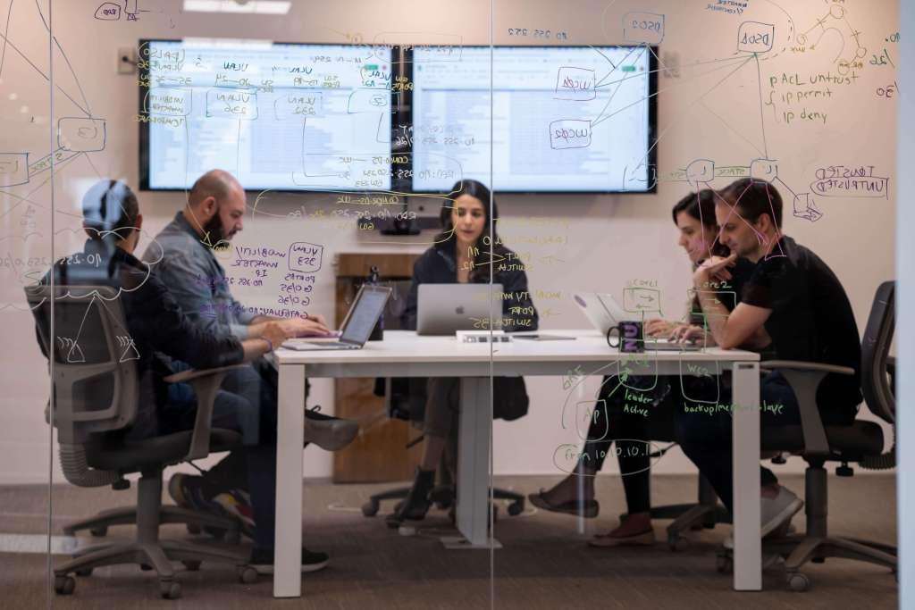 ESG: Trabajadores sentados al rededor de una mesa blanca que se encuentra al interior de una sala de juntas