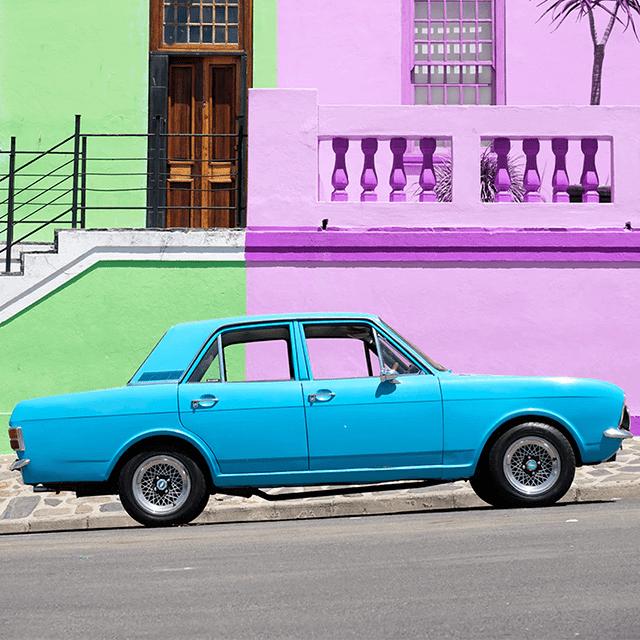 el mejor momento para comprar un auto: vehiculo azél estacionado frente a pared morada