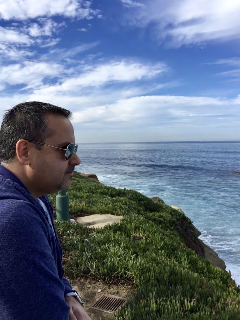 Hombre con gafas y sweater azul mira hacia el mar desde un risco disfrutando de tu tiempo libre al rechazar a la banca tradicional