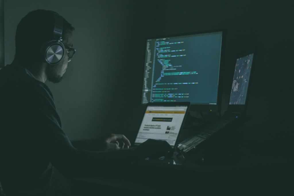 Hombre de edad mediana trabaja en códigos con su computadora y algunos monitores para evitar fraudes al descargar apps