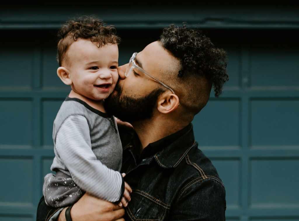 Hombre adulto con gafas sostienen y besa a un niño pequeño vestido con playera color gris frente a un pórtico: ¿Cómo funciona un seguro de vida?
