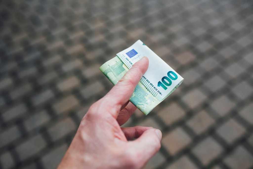 Mano sostiene un billete de cien, ofreciéndolo como dinero fácil: Pirámide financiera