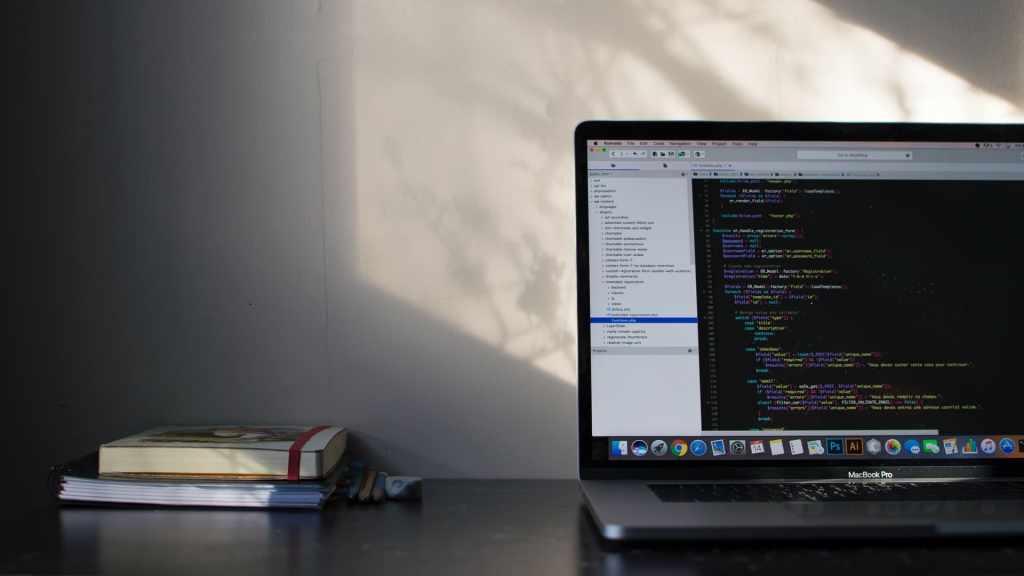 Computadora abierta sobre escritorio muestra códigos de programación para proteger tu vida en línea