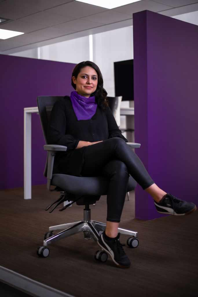 Verónica Urzúa vestida de negro con pañuelo morado está sentada en las oficinas centrales de Nu México y habla sobre el día internacional de la mujer