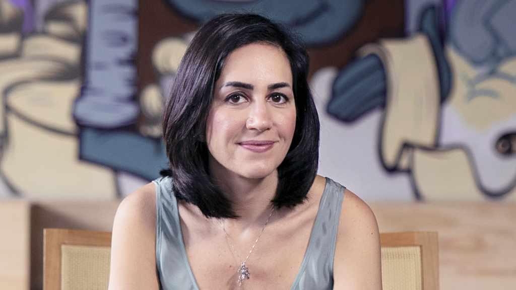 Cristina Junqueira cofundadora de Nubank sentada frente a mural de Nu Brasil anuncia compromiso por mujeres