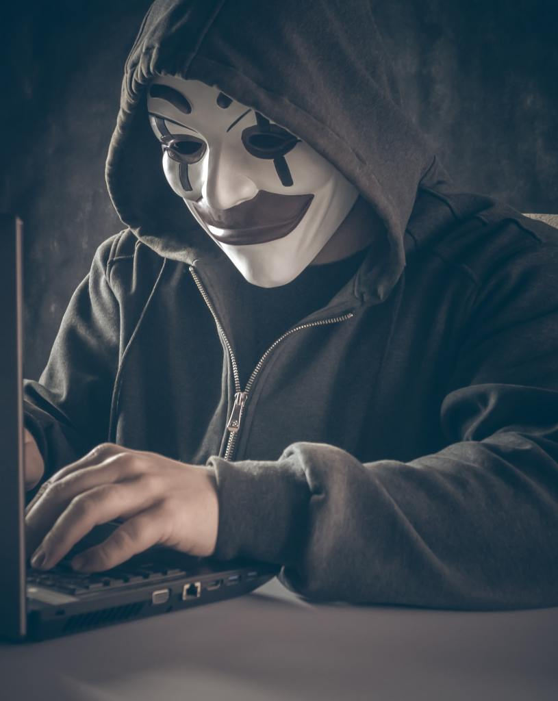 Persona con chamarra negra usando una máscara en la computadora simula ser una delincuente virtual que comete scam o scamming
