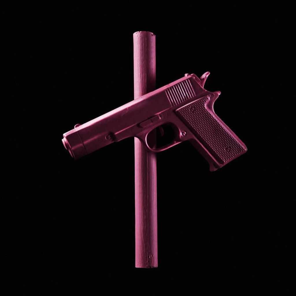 Arma de fuego y palo formando una cruz, imagen parte de la serie elaborada por Cruces Por Rosas