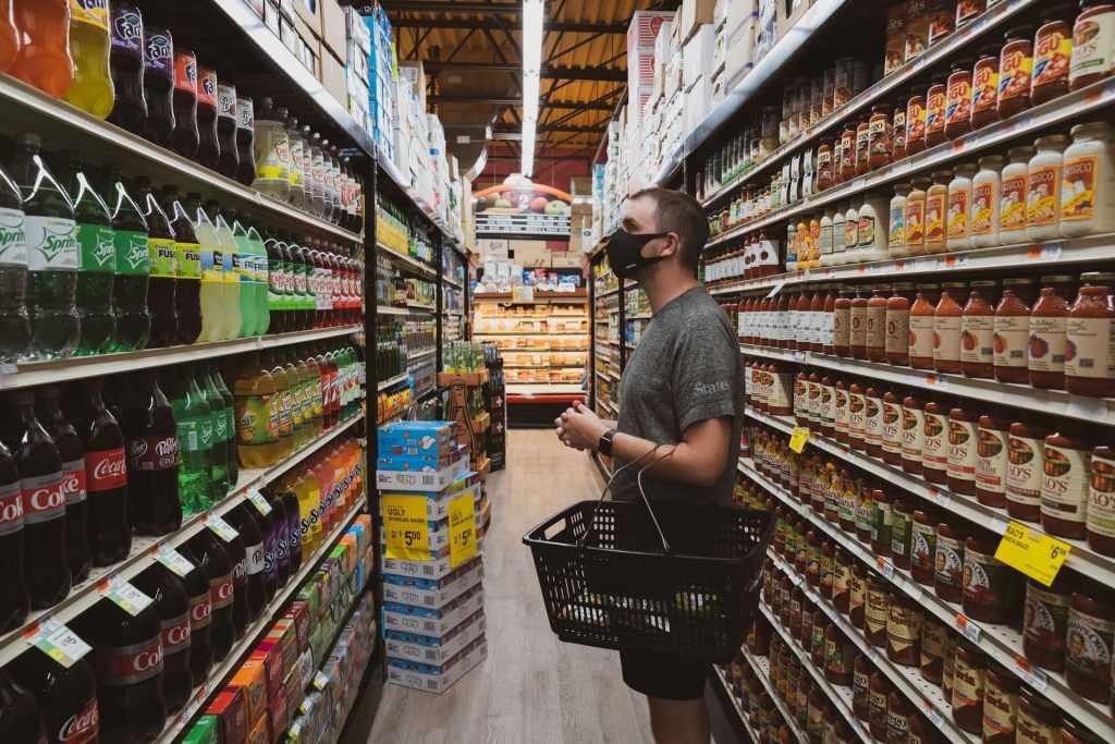 """Hombre de edad mediana parado en en pasillo de supermercado mira anaqueles con refrescos de varias marcas y se pregunta: ¿Qué es mejor?¿Planificar """"el gasto"""" semanal o mensual?"""