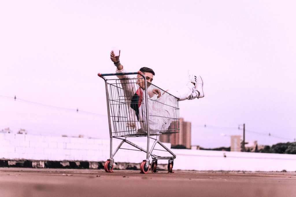 Joven de mediana edad vestido de blanco dentro de un carrito de supermercado saluda y anuncia Compras Diferidas en Nu