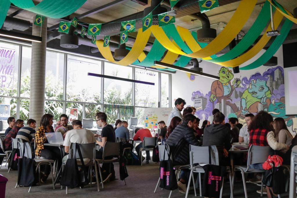 Sala DayOne do Nubank, decorada em verde e amarelo, com pessoas sentadas em mesas e trabalhando no computador no primeiro dia de trabalho delas.