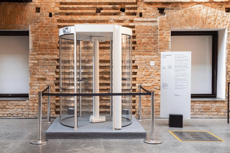 Porta giratória de banco em exibição como peça de museu dentro da Pinacoteca do Estado de São Paulo. A porta está encostada em uma parede de tijolos com fitas de segurança ao redor. Ao lado, uma placa com um manifesto contra a burocracia para anunciar o Débito Nubank