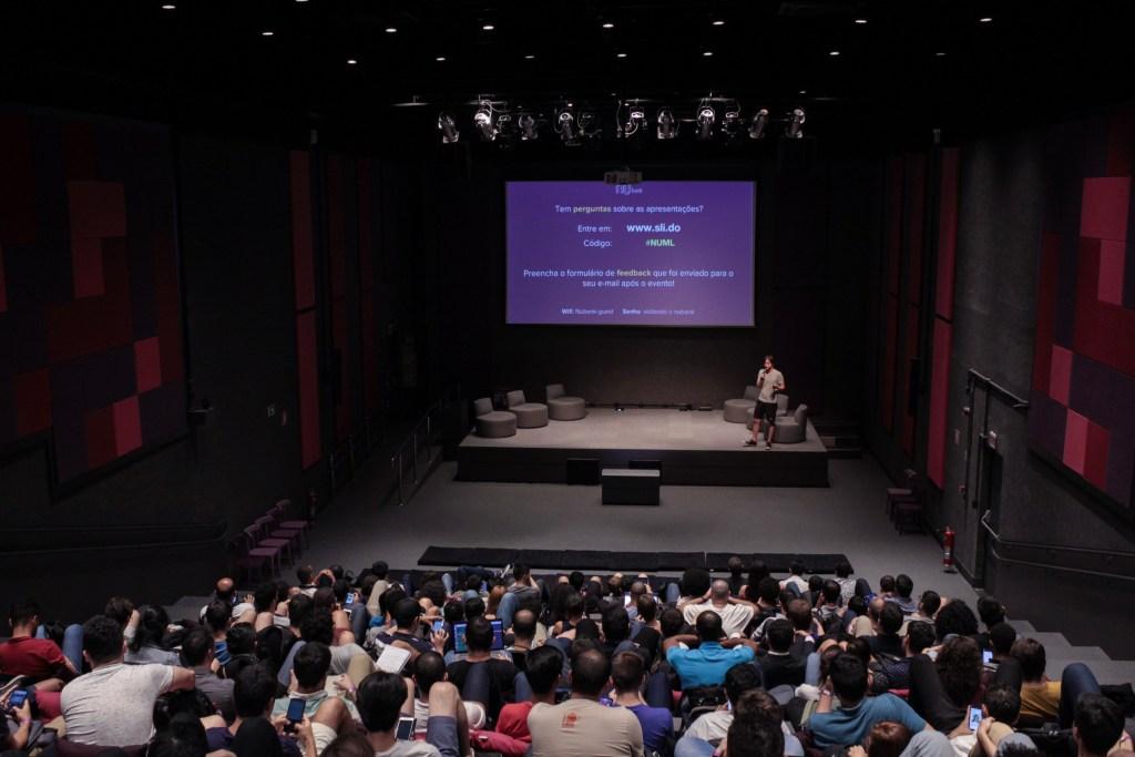 Encontro de Machine Learning no auditório do Nubank. A foto mostra os espectadores de costas e, ao fundo, um palestrante no palco