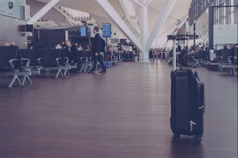 Imagem mostra o saguão de um aeroporto quase vazio e uma mala, sozinha, em primeiro plano