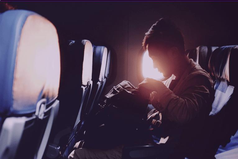 Foto mostra passageiro sentado na janelinha do avião, mexendo em uma mochila, e com o sol alaranjado visto pelo vidro