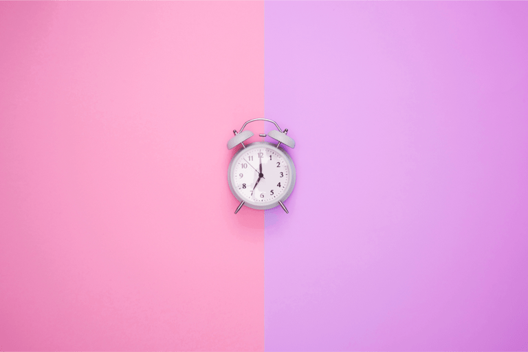 Relógio de ponteiro branco sobre um fundo metade rosa e metade roxo