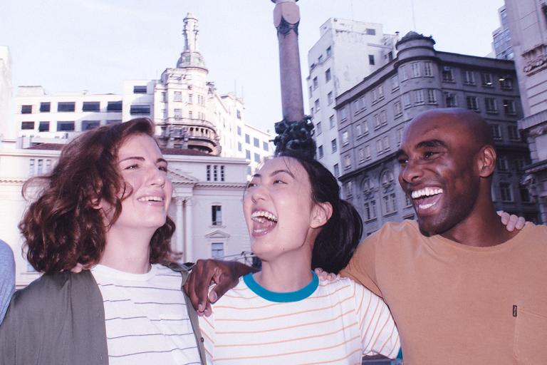 Quatro amigos se abraçam e sorriem no centro de São Paulo: um deles usa boné e camiseta azul; ao seu lado, uma garota ruiva de blusa listrada, uma morena também de camiseta listrada, e um homem de camiseta marrom.