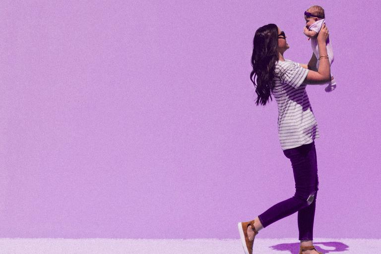 Em um fundo roxo claro, uma mulher morena de camiseta segura uma bebê na altura de seu rosto.