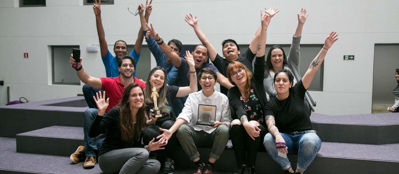 Grupo de Nubankers del departamento de servicio al cliente alzan los brazos en las oficinas de Nubank Brasil