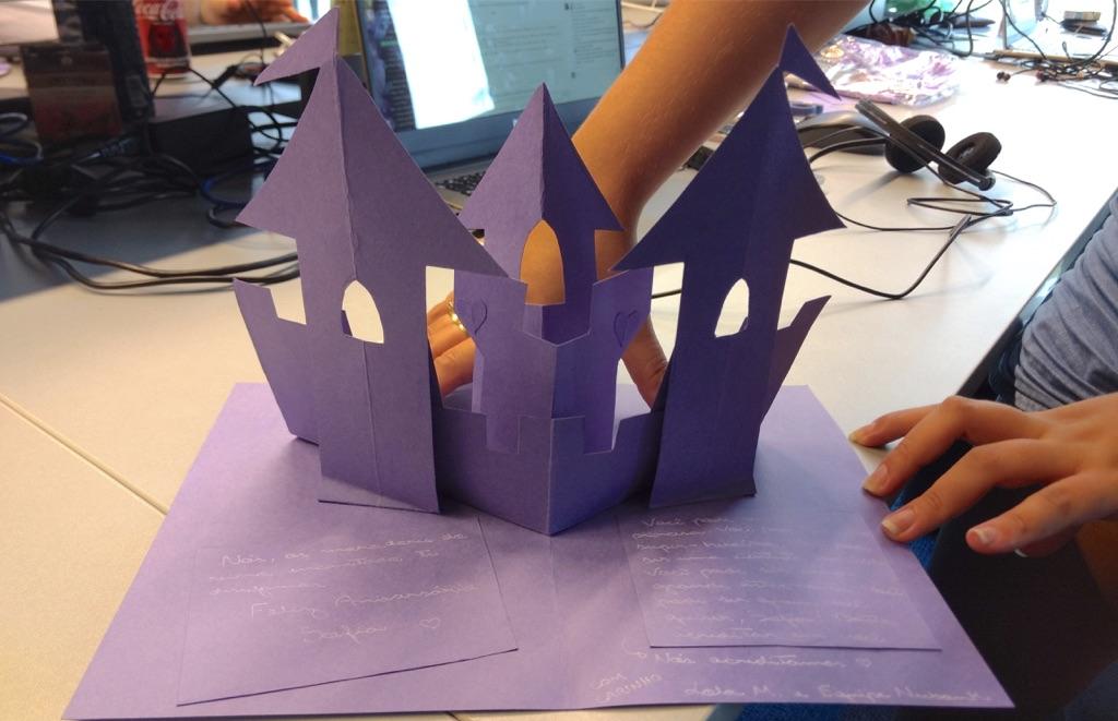 Cartinha escrita à mão em papel roxo, em forma de castelo.