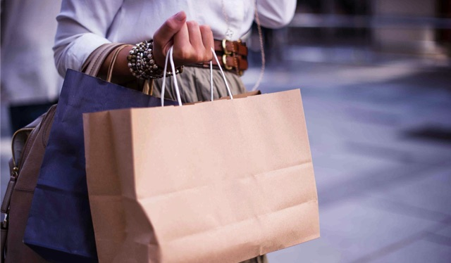 Black Friday 2019: jovem com pulseiras segura sacolas de compras
