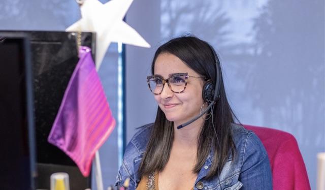 Vagas Nubank: jovem sentada em frente ao computador, de óculos, sorrindo