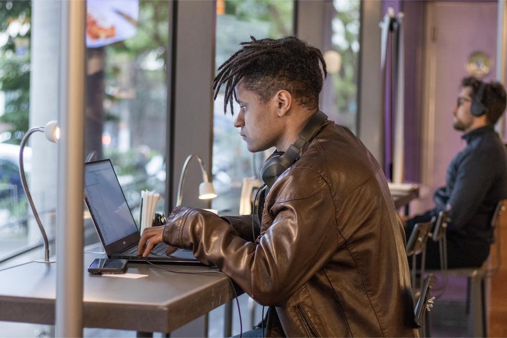 Vagas Nubank: jovem sentado em frente ao computador, trabalhando em um café
