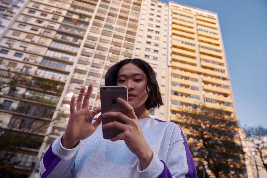 Negociar dividas: mulher em frente a um prédio olhando o celular