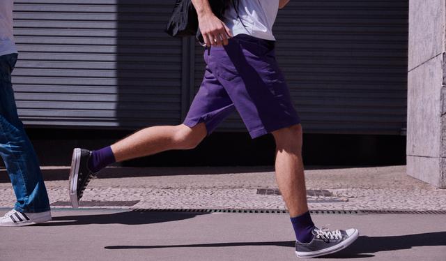 Um homem (da cintura pra baixo) correndo com meias e bermuda roxas, camiseta branca e mochila nas costas.