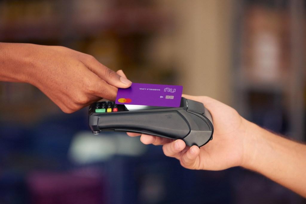 Conta PJ Nubank: uma pessoa segura uma maquininha de cartão preta com a mão direita. Uma outra aproxima o cartão de crédito Nubank da maquininha.