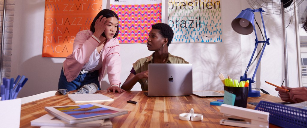 Metodologia ágil: foto mostra duas jovens conversando em frente a uma parede de post its. Uma delas está sentada em uma mesa, com um computador aberto