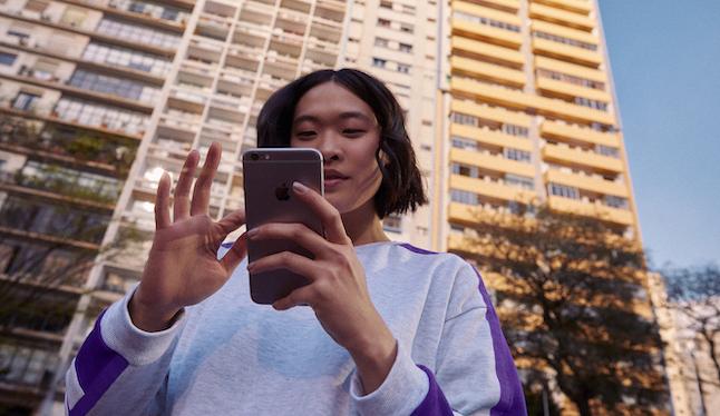 NuConta: jovem de cabelos curtos e blusa branca usa seu telefone